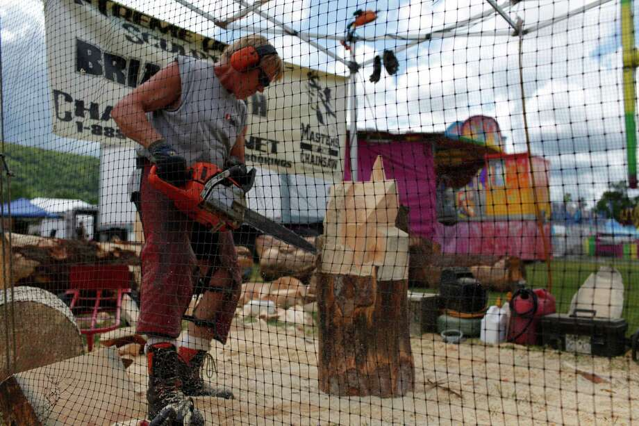 Chainsaw sculptor Brian Ruth works on one of his creations for opening day at the Schoharie County Fair, Friday July 27, 2012 in Cobleskill, N.Y. (Dan Little/Special to the Times Union) Photo: Dan Little / Dan Little