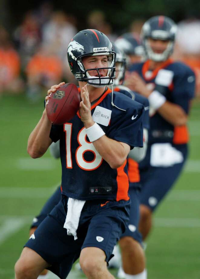 Denver Broncos quarterbacks Peyton Manning, front, Caleb Hanie, center, and Brock Osweiler take part in drills at the team's training camp in Englewood, Colo., on Friday, July 27, 2012. (AP Photo/David Zalubowski) Photo: David Zalubowski