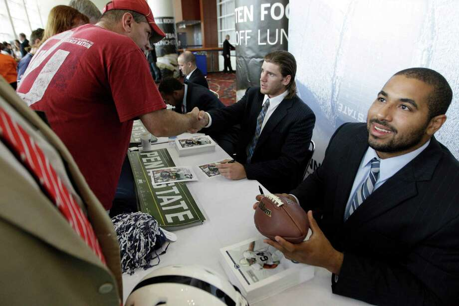 Penn State football players Michael Mauti and John Urschel, right, sign autographs for fans as part of Big Ten Media Days and Kickoff Luncheon, Friday, July 27, 2012, in Chicago. (AP Photo/M. Spencer Green) Photo: M. Spencer Green