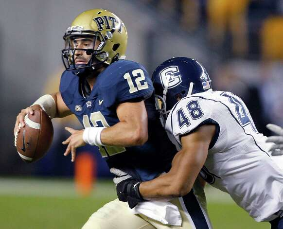 Pittsburgh quarterback Tino Sunseri (12) is sacked by Connecticut defensive end Trevardo Williams (48) in the second quarter of an NCAA college football game Wednesday, Oct. 26, 2011, in Pittsburgh. (AP Photo/Keith Srakocic) Photo: Keith Srakocic, Associated Press / AP