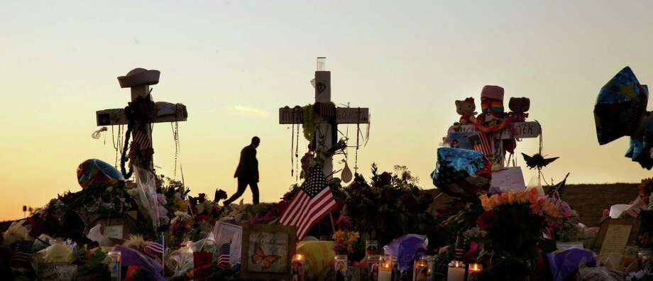 "A man walks on a hill near crosses set up at the memorial to victims of the Aurora, Colo., movie theater shooting, a week after a gunman opened fire during a late-night showing of ""The Dark Knight Rises"" Batman movie, killing 12 and injuring dozens of others on July 22, 2012.  Photo: Ted S. Warren, Associated Press / AP"