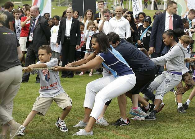 Michelle Obama plays tug-of-war during a Let's Move event for U.S. military children and U.S. and British students in London before the Summer Olympics. Mackey's company works with the first lady via a foundation. Photo: Lefteris Pitarakis, Associated Press