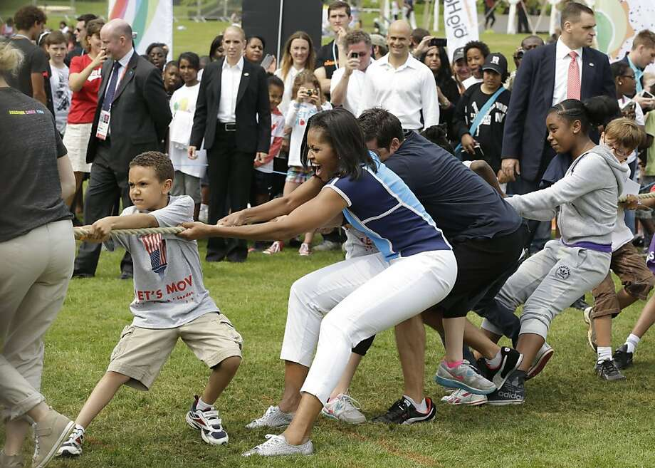 U.S. first lady Michelle Obama plays with schoolchildren during a 'Let's Move!' event for about 1,000 American military children and American and British students at the U.S. ambassador's residence in London, ahead of the 2012 Summer Olympics, Friday, July 27, 2012.  Photo: Lefteris Pitarakis, Associated Press