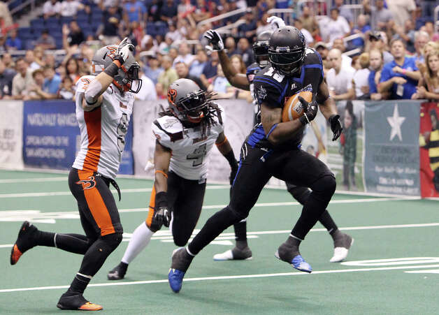San Antonio Talons' Derek Lee (18) pulls away from Utah Blaze's David Hyland (09) and Alfred Phillips (04) for a touchdown in the first half of their quarterfinal AFL National Conference playoff game at the Alamodome on Friday, July 27, 2012. Photo: Kin Man Hui, San Antonio Express-News / ©2012 San Antonio Express-News