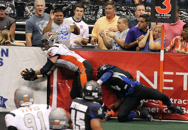 Utah Blaze's Tysson Poots (19) extends to score a touchdown against the San Antonio Talons' Kenneth Fontenette (04) in the first half of their quarterfinal AFL National Conference playoff game at the Alamodome on Friday, July 27, 2012. Photo: Kin Man Hui, San Antonio Express-News / ©2012 San Antonio Express-News