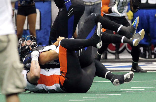 San Antonio Talons' Aaron Garcia (08) gets sacked in a crucial fourth-down play in the fourth quarter by Utah Blaze's Joe Mortensen (42) in their quarterfinal AFL National Conference playoff game at the Alamodome on Friday, July 27, 2012. The Blaze won, 35-34, to end the inaugural season for the Talons in San Antonio. Photo: Kin Man Hui, San Antonio Express-News / ©2012 San Antonio Express-News