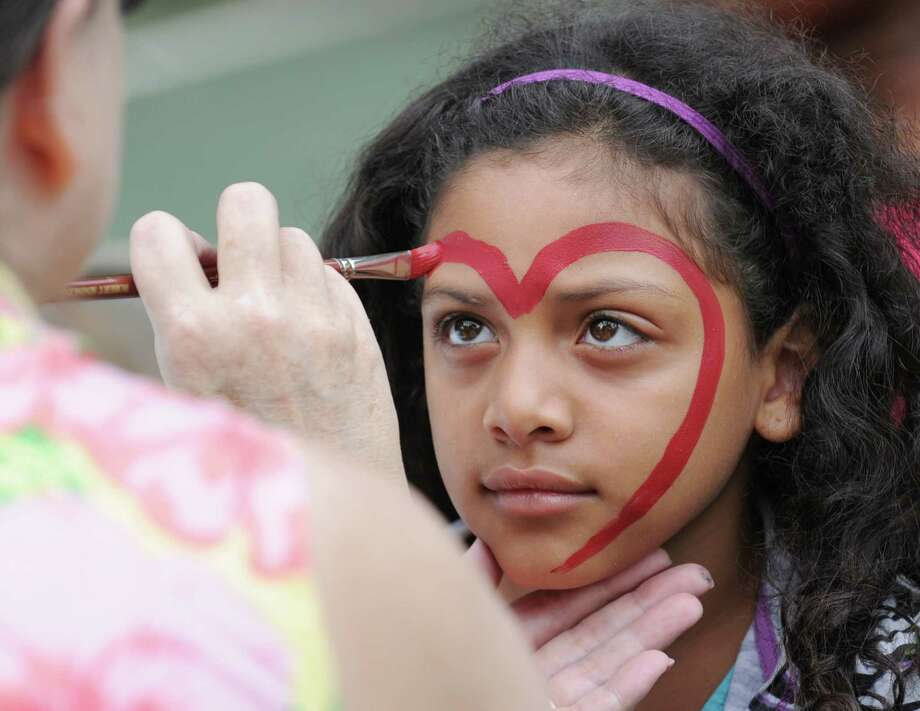 Artist Patricia Muldoon, left, paints a heart onto the face of Gigi Vargas, 8, of Greenwich, during the Greenwich Baptist Church and Greenwich Housing Authority jointly hosted annual block party at Wilbur Peck Court in Greenwich, Saturday, July 28, 2012. Photo: Bob Luckey / Greenwich Time