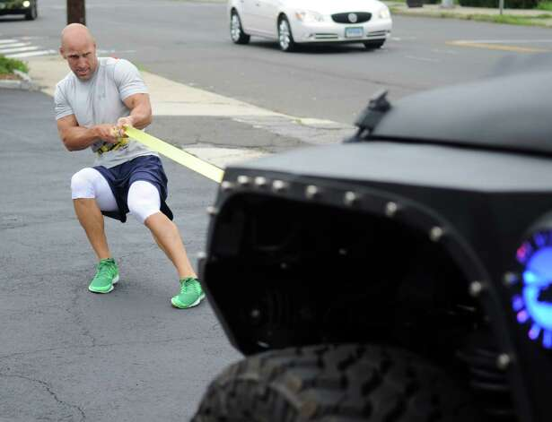 Bobby Darula leans back as he pulls a Jeep during a free, boot camp-style workout session in Stamford on Saturday, July 28, 2012. The event was held by Tommy K's Vitamins and Longevity LLC to raise money for a scholarship set up by the family of Stamford resident and Navy SEAL Brian Bill, who was killed in August, 2011, while deployed in Afghanistan. Photo: Lindsay Niegelberg / Stamford Advocate