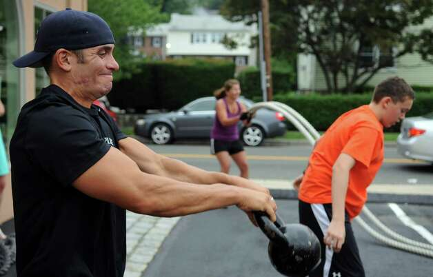 Richard Gasparino participates in a free, boot camp-style workout session in Stamford on Saturday, July 28, 2012. The event was held by Tommy K's Vitamins and Longevity LLC to raise money for a scholarship set up by the family of Stamford resident and Navy SEAL Brian Bill, who was killed in August, 2011, while deployed in Afghanistan. Photo: Lindsay Niegelberg / Stamford Advocate