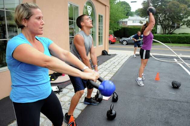 Maureen Adams, left, participates in a free, boot camp-style workout session in Stamford on Saturday, July 28, 2012. The event was held by Tommy K's Vitamins and Longevity LLC to raise money for a scholarship set up by the family of Stamford resident and Navy SEAL Brian Bill, who was killed in August, 2011, while deployed in Afghanistan. Photo: Lindsay Niegelberg / Stamford Advocate