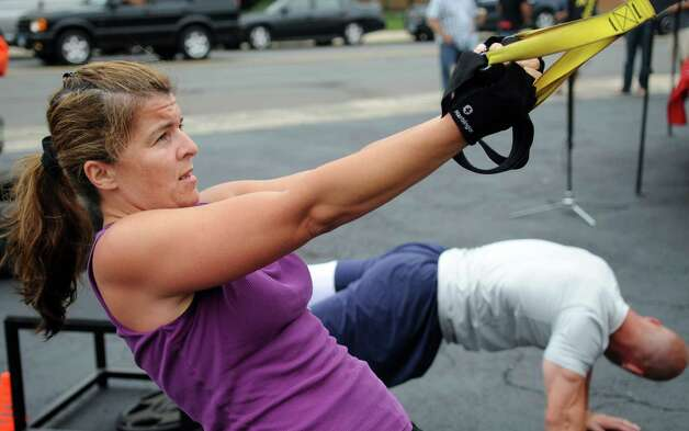Colleen Sharkey works out during a free, boot camp-style workout session in Stamford on Saturday, July 28, 2012. The event was held by Tommy K's Vitamins and Longevity LLC to raise money for a scholarship set up by the family of Stamford resident and Navy SEAL Brian Bill, who was killed in August, 2011, while deployed in Afghanistan. Photo: Lindsay Niegelberg / Stamford Advocate