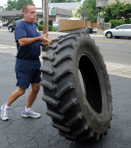 Frank Piro flips a tire during a free, boot camp-style workout session in Stamford on Saturday, July 28, 2012. The event was held by Tommy K's Vitamins and Longevity LLC to raise money for a scholarship set up by the family of Stamford resident and Navy SEAL Brian Bill, who was killed in August, 2011, while deployed in Afghanistan. Photo: Lindsay Niegelberg / Stamford Advocate