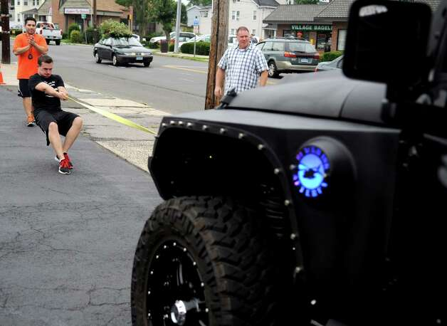 Matt Jones leans back as he pulls a Jeep during a free, boot camp-style workout session in Stamford on Saturday, July 28, 2012. The event was held by Tommy K's Vitamins and Longevity LLC to raise money for a scholarship set up by the family of Stamford resident and Navy SEAL Brian Bill, who was killed in August, 2011, while deployed in Afghanistan. Photo: Lindsay Niegelberg / Stamford Advocate