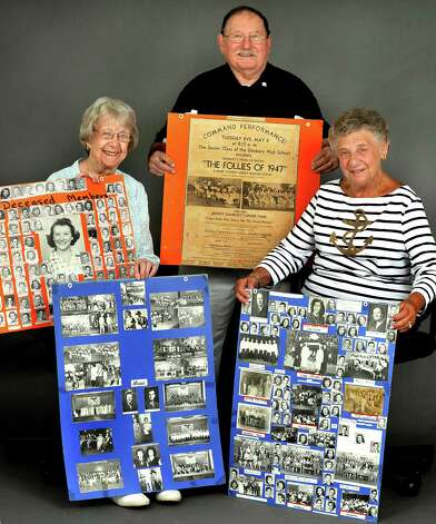Sally Wilkes, left, Michael Timan, and Irene Menzer, hold memorabilia of the Danbury High School Class of 1947 as they talk about their upcomming 65th reunion Saturday, July 28, 2012. Photo: Michael Duffy / The News-Times