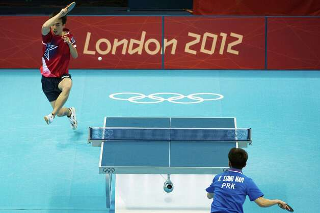 Timothy Wang of Houston makes a return against Kim Song Nam of the People's Republic of Korea in the men's singles preliminary round of table tennis at the 2012 London Olympics on Saturday, July 28, 2012. Photo: Smiley N. Pool, Houston Chronicle / © 2012  Houston Chronicle