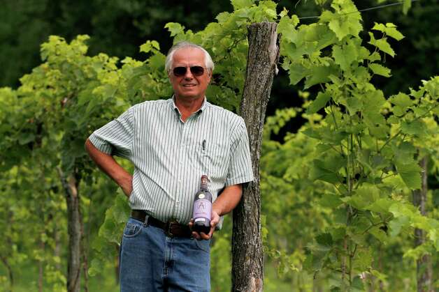 Joe Messina, owner of Amici Vineyards, stands for a portrait with a bottle of his Cabernet Franc Reserve Thursday, July 26, 2012 in Valley Falls, N.Y. (Dan Little/Special to the times Union) Photo: Dan Little / Dan Little