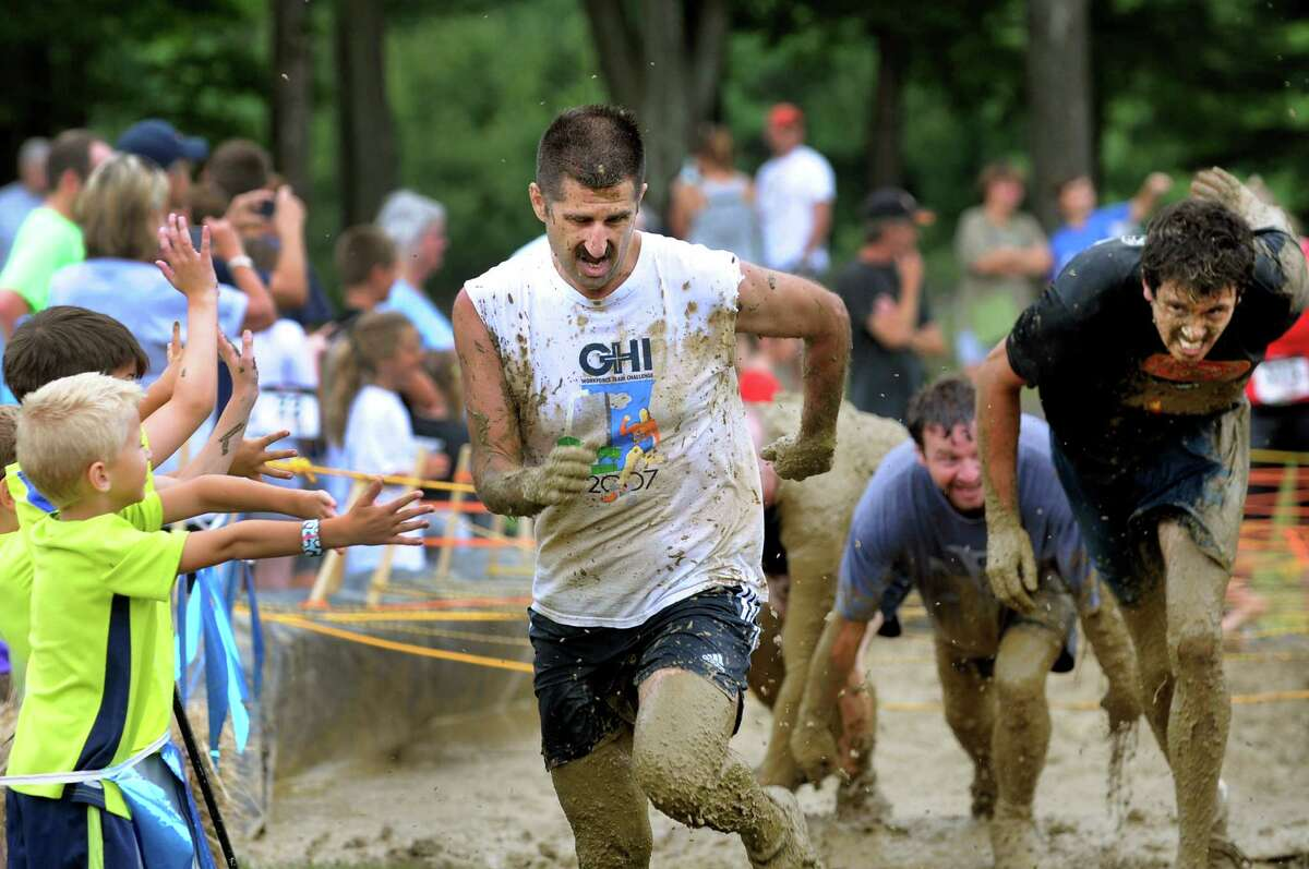Dave Banas of Delmar, center, beats Pete Yarema of Slingerlands, right, out of the mud pit and across the finish line during Run the Ridge 5K Mud Run on Saturday, July 28, 2012, at Maple Ski Ridge in Rotterdam, N.Y. Proceeds went to the Albany Veterans Center, which offers services to local veterans and active military people. (Cindy Schultz / Times Union)