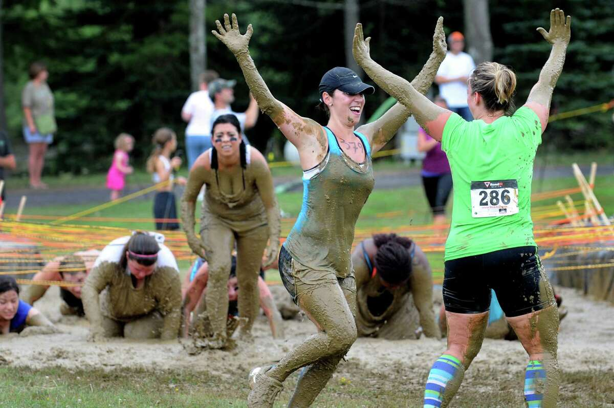 Michele Sobieski, center, does a celebratory dance with Elizabeth Moya, right, after getting through the mud pit during Run the Ridge 5K Mud Run on Saturday, July 28, 2012, at Maple Ski Ridge in Rotterdam, N.Y. Proceeds went to the Albany Veterans Center, which offers services to local veterans and active military people. (Cindy Schultz / Times Union)