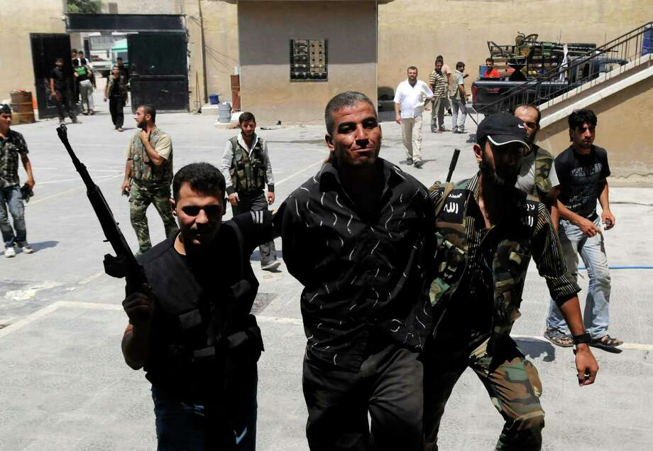 In this photograph made on  Friday, July 27, 2012, Syrian rebels arrest a man who they said was a government informant  in Aleppo, Syria. Photo: AP