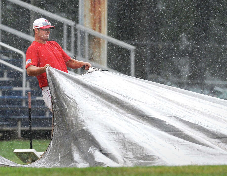 Mike Abate, head coach of the Greenwich Cannons American Legion baseball team, helps put tarp on the infield during a rain storm at Cubeta Stadium in Stamford Saturday afternoon, July 28, 2012. The American Legion State Tournament game between the Greenwich Cannons and Unionville was postponed because of the rain and will be played at 9:30 a.m. Sunday at Cubeta Stadium. Photo: Bob Luckey / Greenwich Time