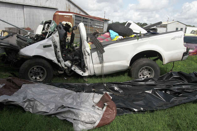 This Monday, July 23, 2012 photo shows what remains of a 2000 Ford F-250 pickup truck after it crashed into a tree on the side of U.S. Highway 59 between Goliad and Beeville, Texas before 7:00 p.m. Sunday evening. The truck, overloaded with nearly two dozen illegal immigrants, veered off a highway and crashed into trees, killing at least 14, authorities said. (AP Photo/San Antonio Express-News, John Davenport)  RUMBO DE SAN ANTONIO OUT; NO SALES Photo: AP
