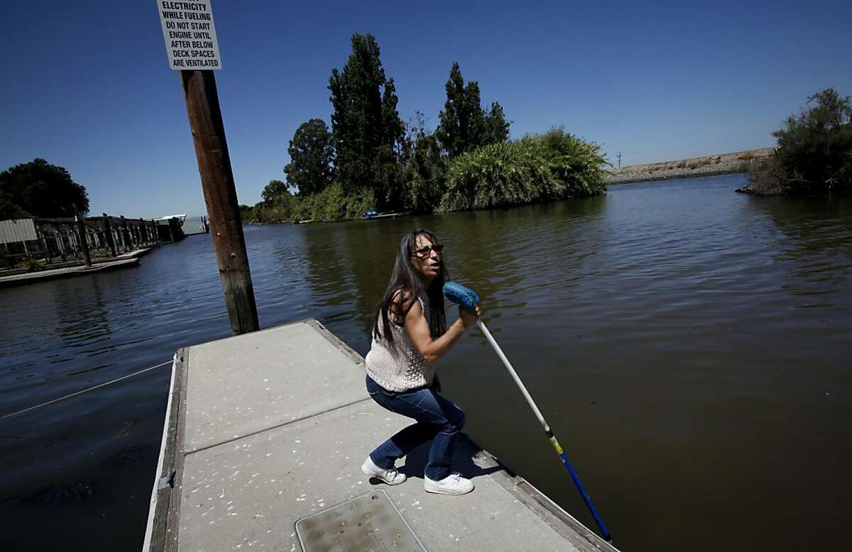 Korinne Flowers, who owns the Tracy Oasis Marina-Resort, uses a pole to show how low the water level is in Tracy, Calif., Friday, July 27, 2012. Flowers is worried any plan to move water to existing pumps that supply water to Southern California, the Central Valley and the Bay Area will lower the water even more and hurt business.