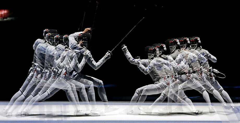 This multiple exposure photo shows Italy's Elisa Di Francisca, left, and South Korea's Nam Hyun-hee competing during a semifinal fencing match at the 2012 Summer Olympics, Saturday, July 28, 2012, in London. (AP Photo/Andrew Medichini) Photo: Andrew Medichini, Associated Press