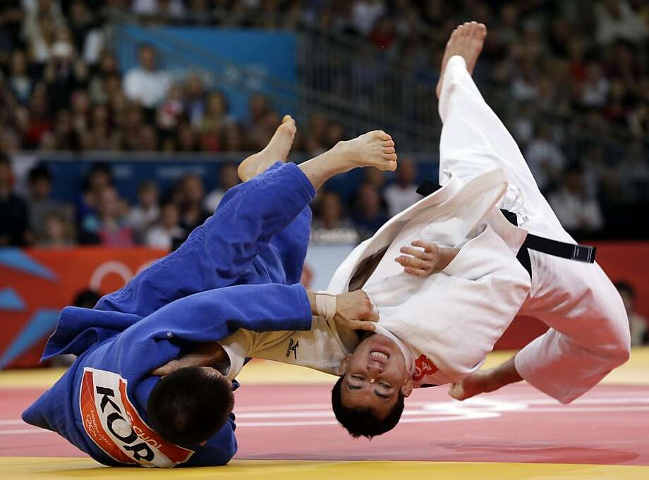 Gwang-Hyeon Choi of the Republic of Korea flips Felipe Kitadai of Brazil during the semifinal round of the men's 60kg judo competition at the 2012 Summer Olympics, Saturday, July 28, 2012, in London. (AP Photo/Paul Sancya) Photo: Paul Sancya, Associated Press