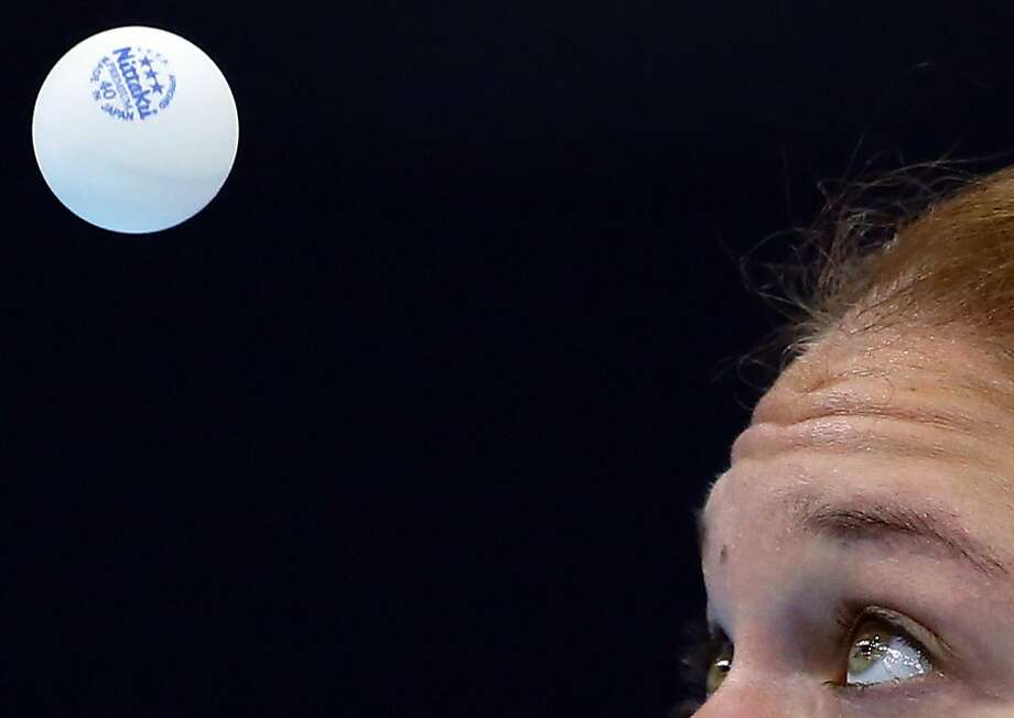 Croatia's Cornelia Molnar keeps her eyes on the ball as she takes a shot against USA's Lily Zhang during a table tennis preliminary round match at the 2012 Summer Olympics, Saturday, July 28, 2012, in London. (AP Photo/Sergei Grits) Photo: Sergei Grits, Associated Press