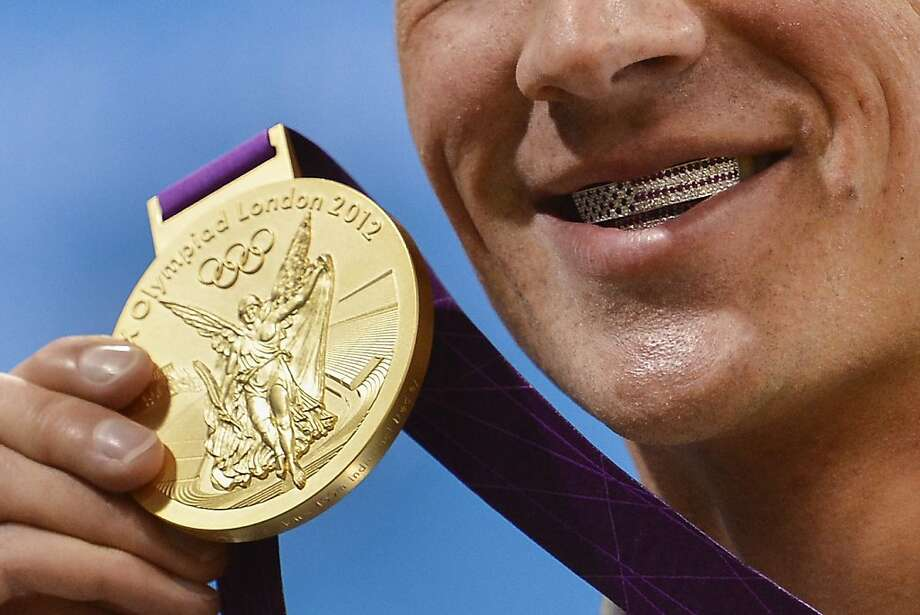 TOPSHOTS US swimmer Ryan Lochte poses with his dental braces bearing the US flag and his gold medal after winning the men's 400m individual medley swimming event at the London 2012 Olympic Games on July 28, 2012 in London. AFP PHOTO / FABRICE COFFRINIFABRICE COFFRINI/AFP/GettyImages Photo: Fabrice Coffrini, AFP/Getty Images