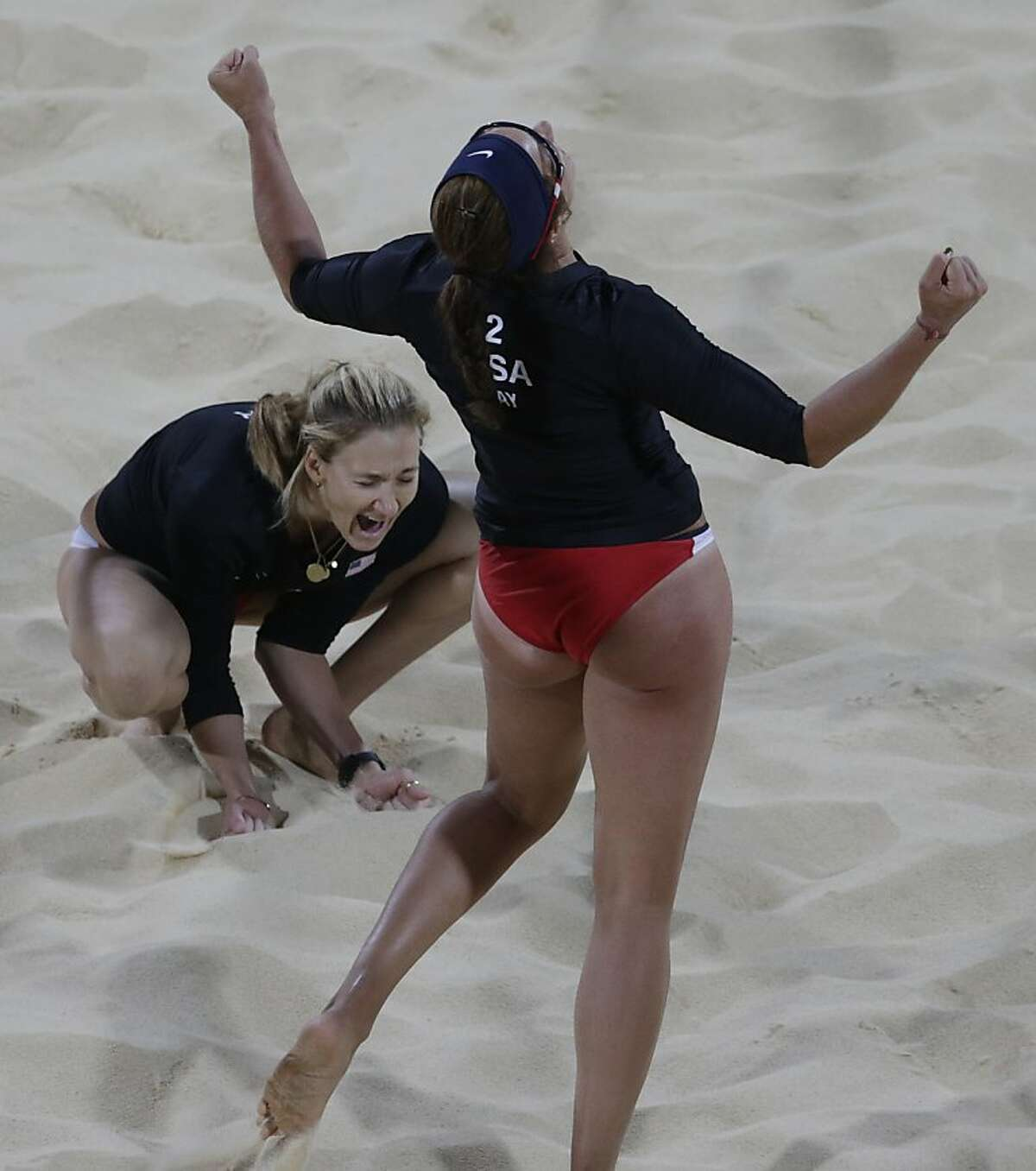Kerri Walsh, left, of the United States reacts with teammate Misty May-Treanor react after beating Australia during a beach volleyball match at the 2012 Summer Olympics, Saturday, July 28, 2012, in London. (AP Photo/Dave Martin)