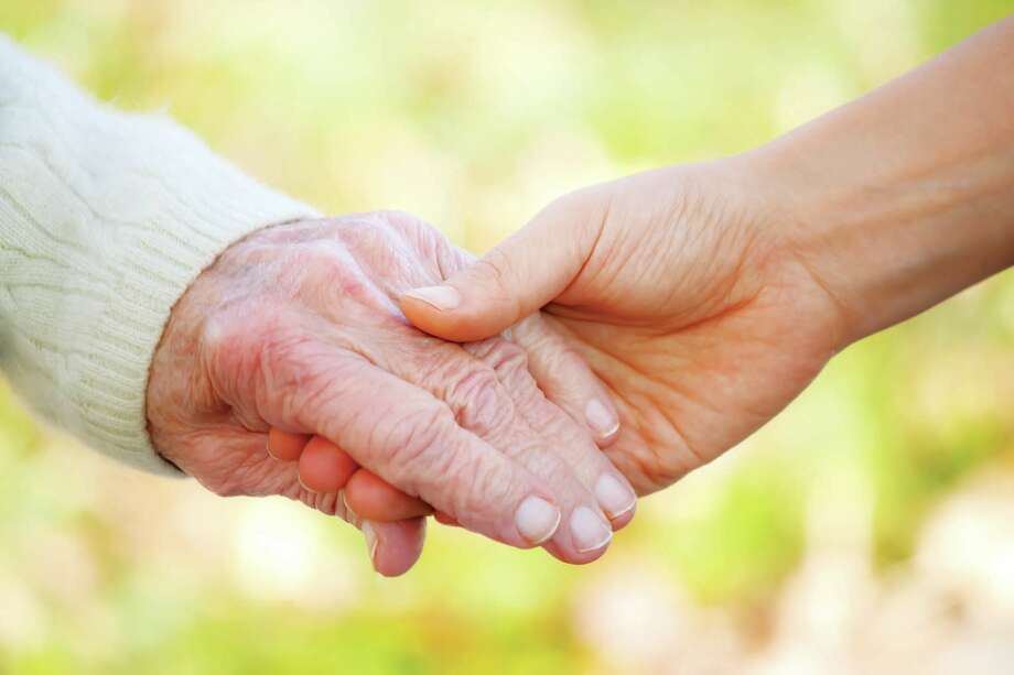 Senior and young holding hands outside. (Fotolia) / Chariclo - Fotolia