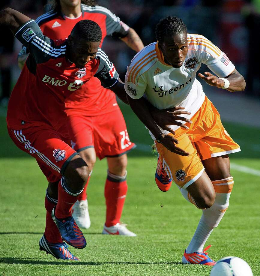 Houston Dynamo's Macoumba Kandji battles Toronto FC's Donell Henry. Photo: Aaron Vincent Elkaim, Associated Press / The Canadian Ptress