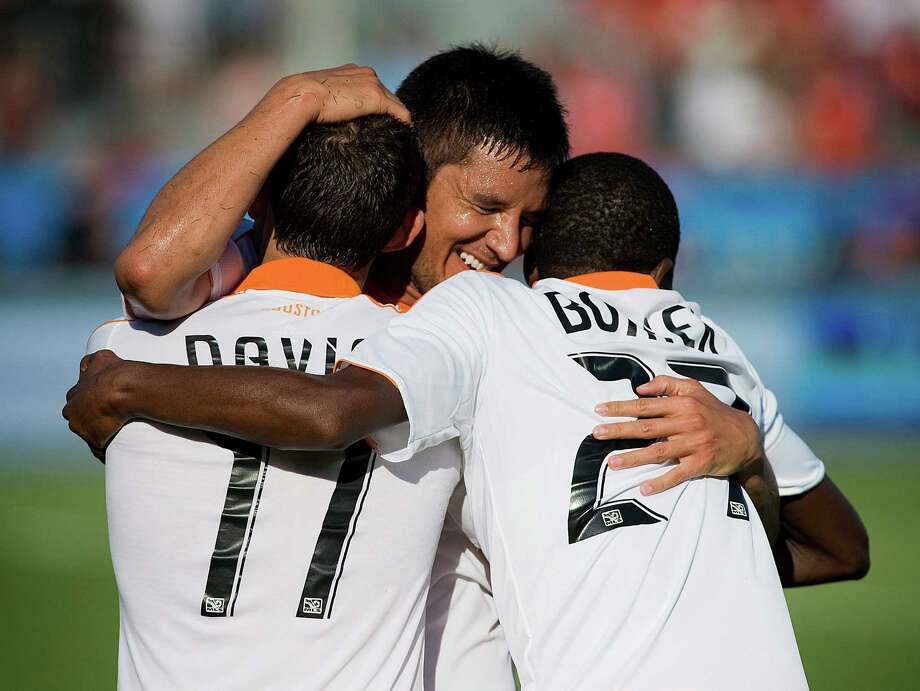 Brian Ching celebrates his second half goal with teammates Brad Davis and Boniek Garcia. Photo: Aaron Vincent Elkaim, Associated Press / CP
