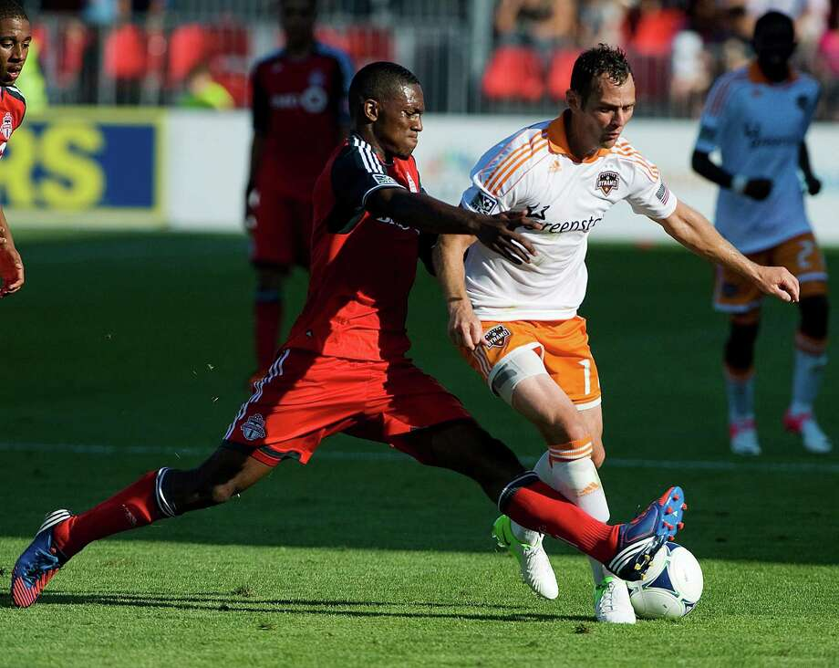 Toronto FC's Donell Henry, left, stretches to take the ball from Brad Davis.  Photo: Aaron Vincent Elkaim, Associated Press / The Canadian Ptress