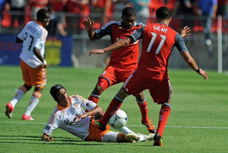 Ashtone Morgan and Luis Silva of the Toronto FC battle for the ball with Calen Carr.  Photo: Brad White, Getty Images / 2012 Getty Images