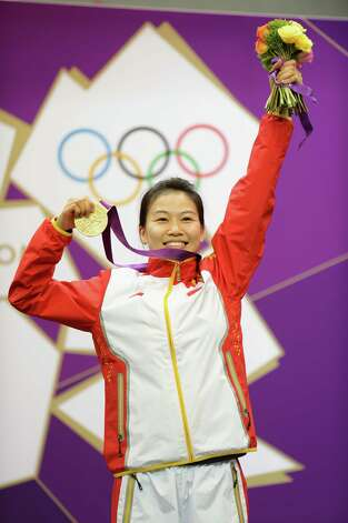 LONDON, ENGLAND - JULY 28:  Gold medalist Siling Yi of China celebrates on the podium during the medal ceremony for the Women's 10m Air Rifle Shooting Final on Day 1 of the London 2012 Olympic Games at The Royal Artillery Barracks on July 28, 2012 in London, England.  Sylwia Bogacka of Poland won silver and Dan Yu of China won bronze.  (Photo by Lars Baron/Getty Images) Photo: Lars Baron, Getty Images / 2012 Getty Images