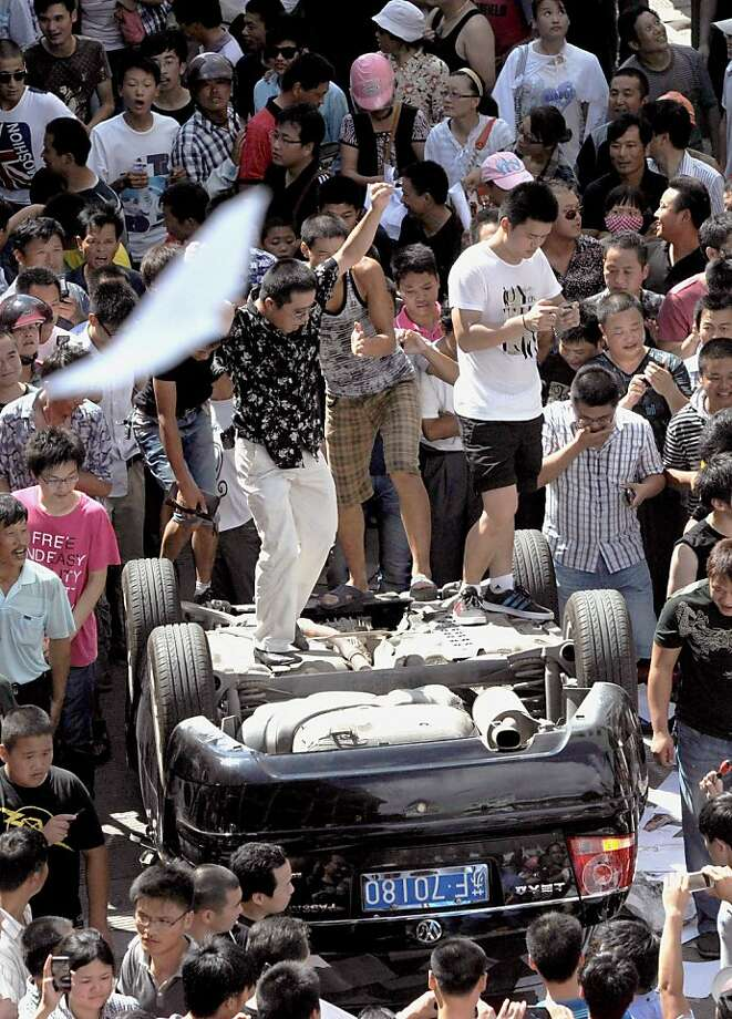 Men stand on an overturned vehicle  as the local residents gather to protest against plans for a water discharge project in Qidong, China Saturday, July 28, 2012. Authorities in eastern China dropped plans for a waste water discharge project Saturday after thousands of protesters angry about pollution took to the streets. It was the latest of many such confrontations in a country where three decades of rapid economic expansion have come at an environmental price.  (AP Photo/Kyodo News) JAPAN OUT, MANDATORY CREDIT, NO LICENSING IN CHINA, HONG KONG, JAPAN, SOUTH KOREA AND FRANCE Photo: Associated Press