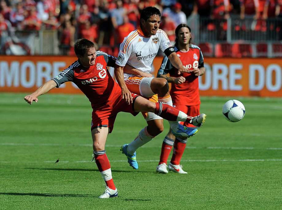 Terry Dunfield of the Toronto FC battles for the ball with Brian Ching. Photo: Brad White, Getty Images / 2012 Getty Images
