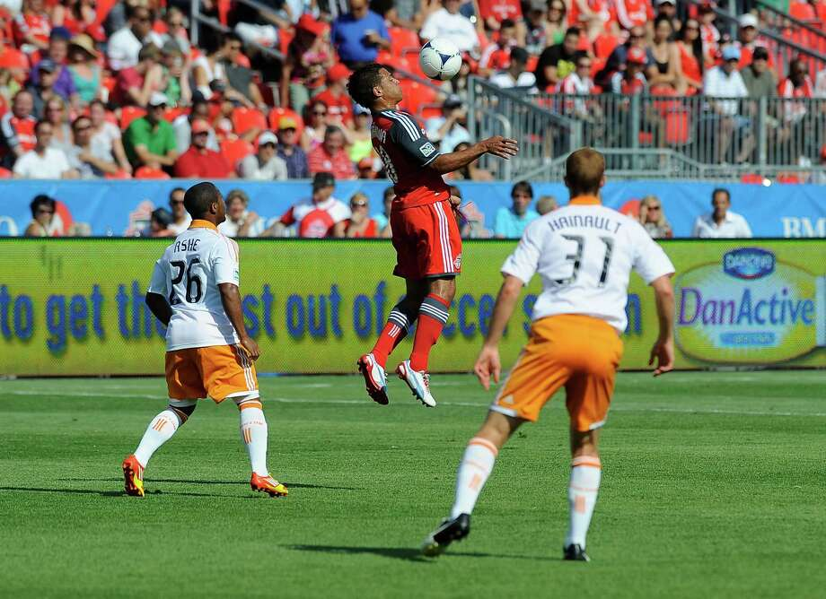 Quincy Amarikwa of the Toronto FC jumps for the ball as Corey Ashe  and Andre Hainault defend. Photo: Brad White, Getty Images / 2012 Getty Images