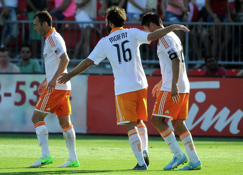 Brad Davis, Adam Moffat and Brian Ching celebrate a second half goal.