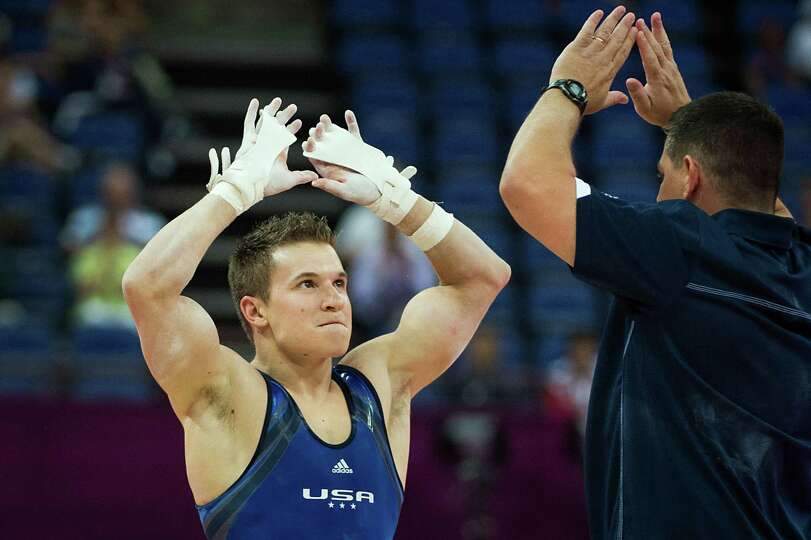 Jonathan Horton celebrates with coach Tom Meadows after his performance on the horizontal bar during