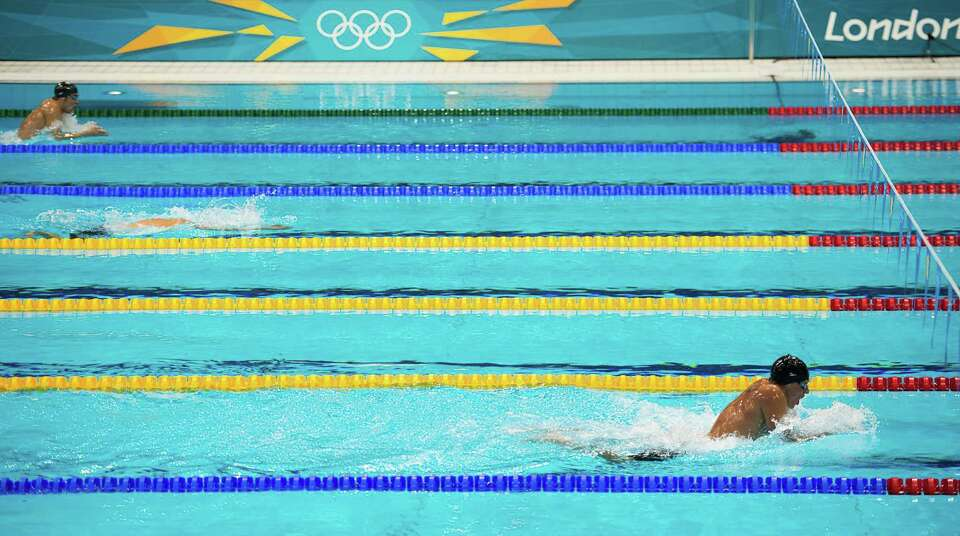 US swimmer Ryan Lochte, bottom, swims well ahead of Michael Phelps, top, during the breast stroke le