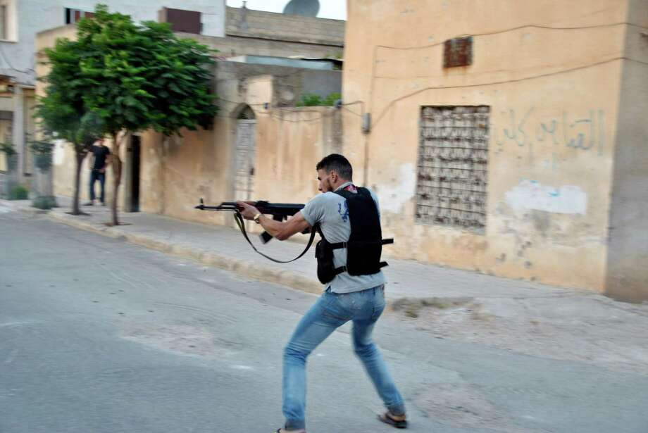 In this Sunday, 22 July, 2012 photo a Syrian rebel fires his weapon during clashes with Syrian troops in Idlib, Syria. (AP Photo/Fadi Zaidan) Photo: Fadi Zaidan
