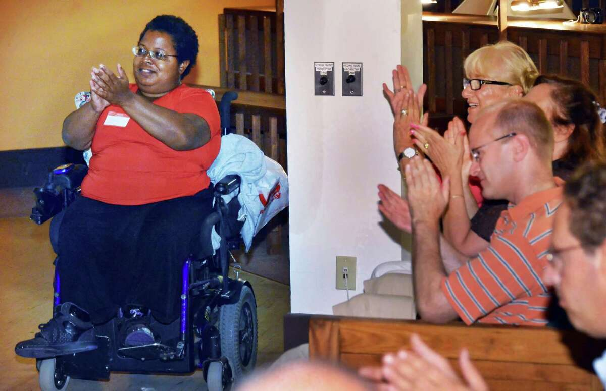Self Advocacy Associations' Shameka Andrews, left, of Albany applauds speakers during an event to call attention to barriers to voting faced by persons with disabilities in Troy Saturday July 28, 2012. holds (John Carl D'Annibale / Times Union)