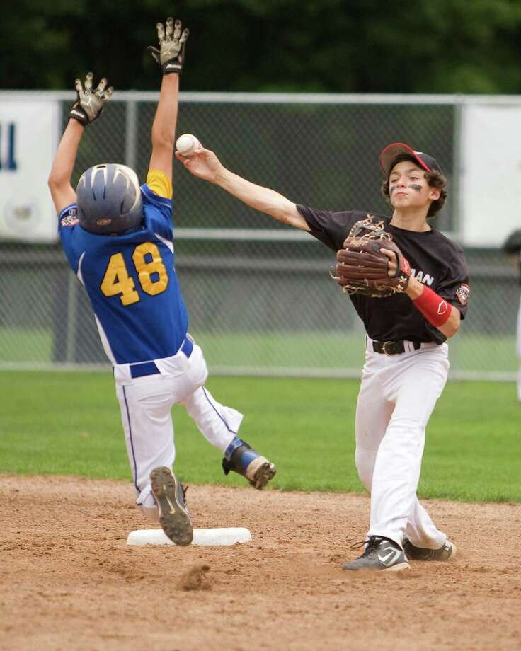 New Canaan shortstop Trevor Donnelly gets the force at second on Newtown's Sam Grossano but is unable to complete the double play in the Cal Ripken 12-year-old New England tournament championship game Saturday at Glander Field in Newtown. Photo: Barry Horn