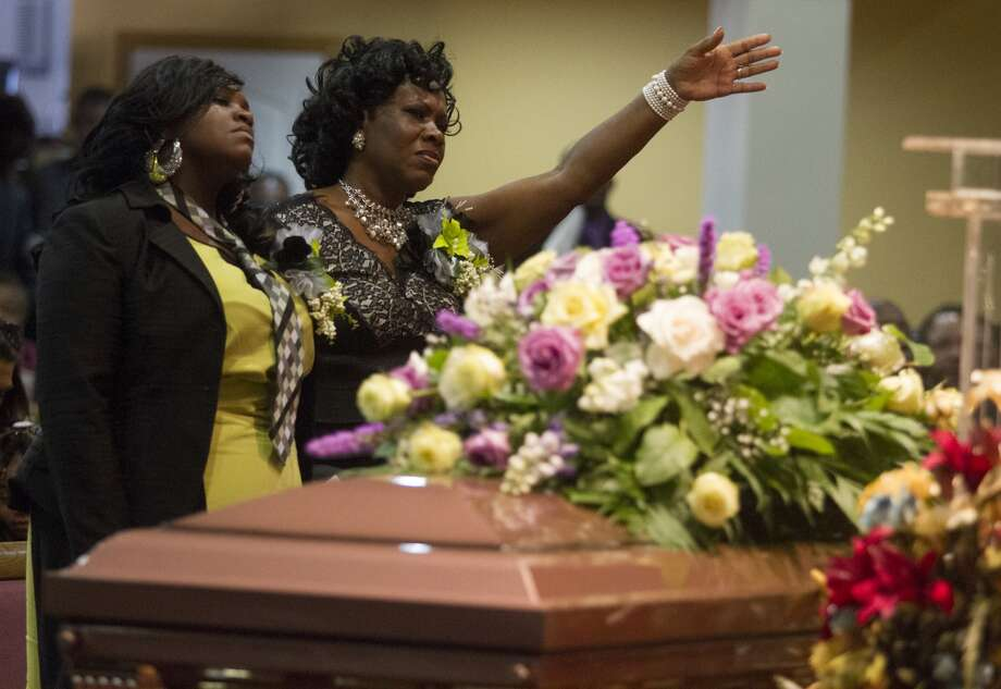 Desmond Jones' wife, Vandaleira, and grandmother Rose Forest pray over Jones' coffin at Living Word Faith Center on July 28. Two suspects killed the minister, 21, as he was returning from a fast-food run and stole his 2012 silver Chrysler 300.