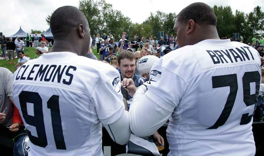 Seahawks' Red Bryant, right, and Chris Clemons, left, sign autographs. Photo: AP