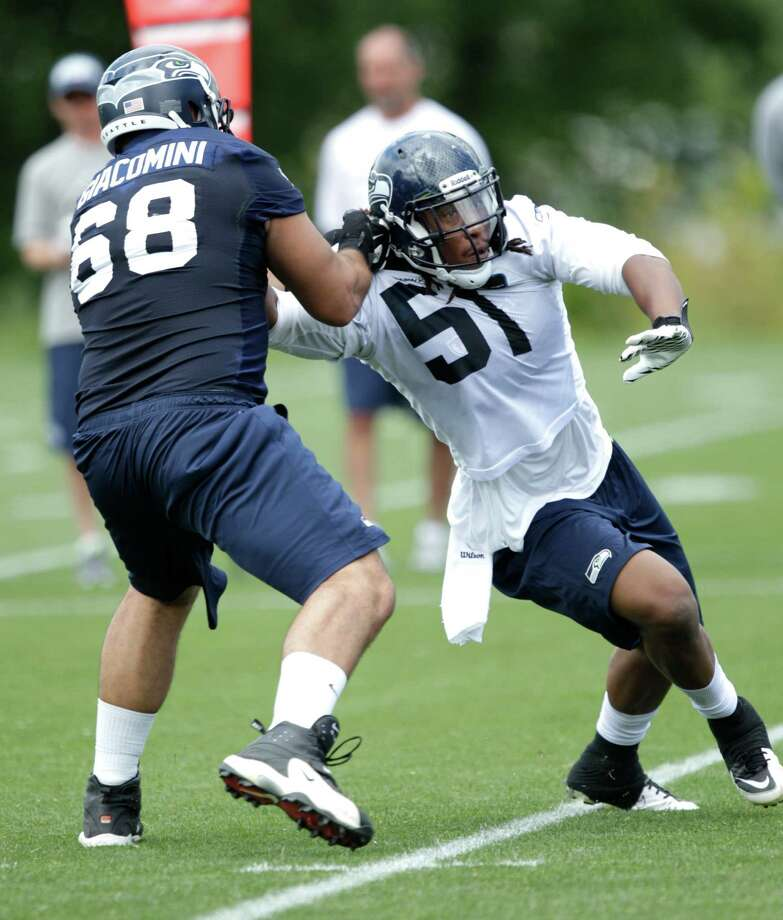 Seahawks defensive end Bruce Irvin, right, is blocked by tackle Breno Giacomini. Photo: AP