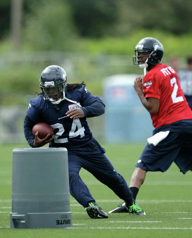 Seahawks running back Marshawn Lynch runs around a trash can during a drill as quarterback Josh Portis looks on at right. Photo: AP